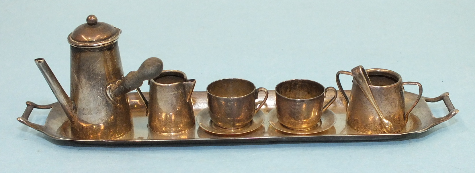 Lot 407 - A miniature silver coffee service, comprising: wooden-handled coffee pot, sugar basin with tongs,