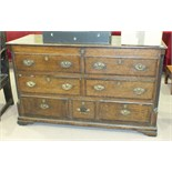 An antique oak mule chest, the hinged lid above two false drawers, one long and three small drawers,