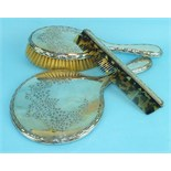 A silver-backed hand mirror, hair brush and comb, Birmingham 1920, (3).