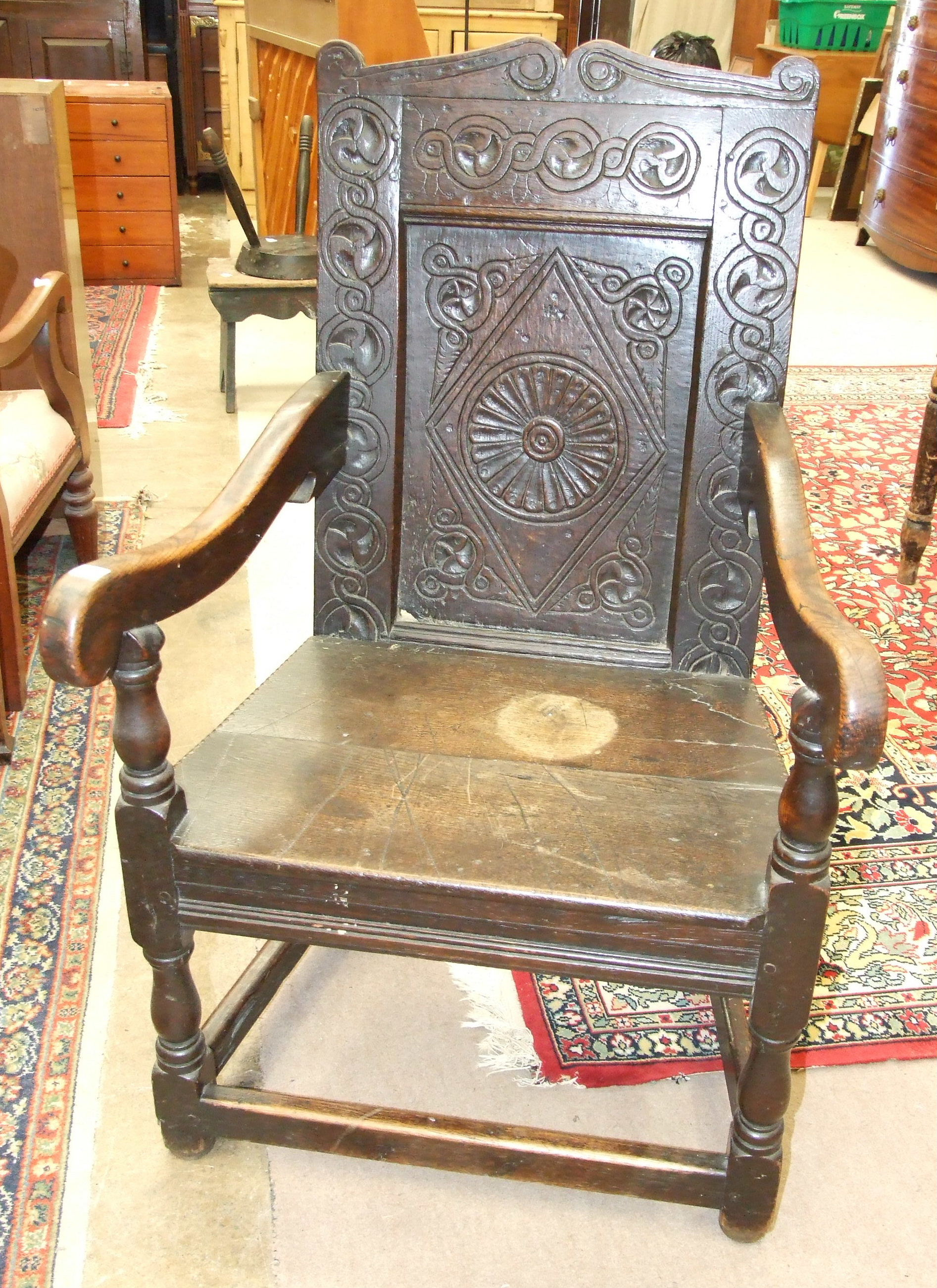 An antique oak armchair, the carved panel back and solid seat on turned legs with stretchers.