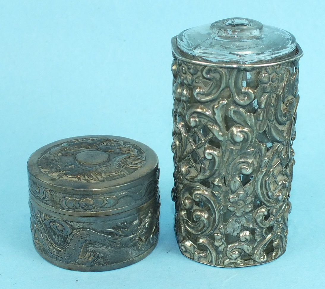 Lot 393 - A Chinese white metal circular pill box and cover embossed with dragon decoration, 4.5cm diameter,