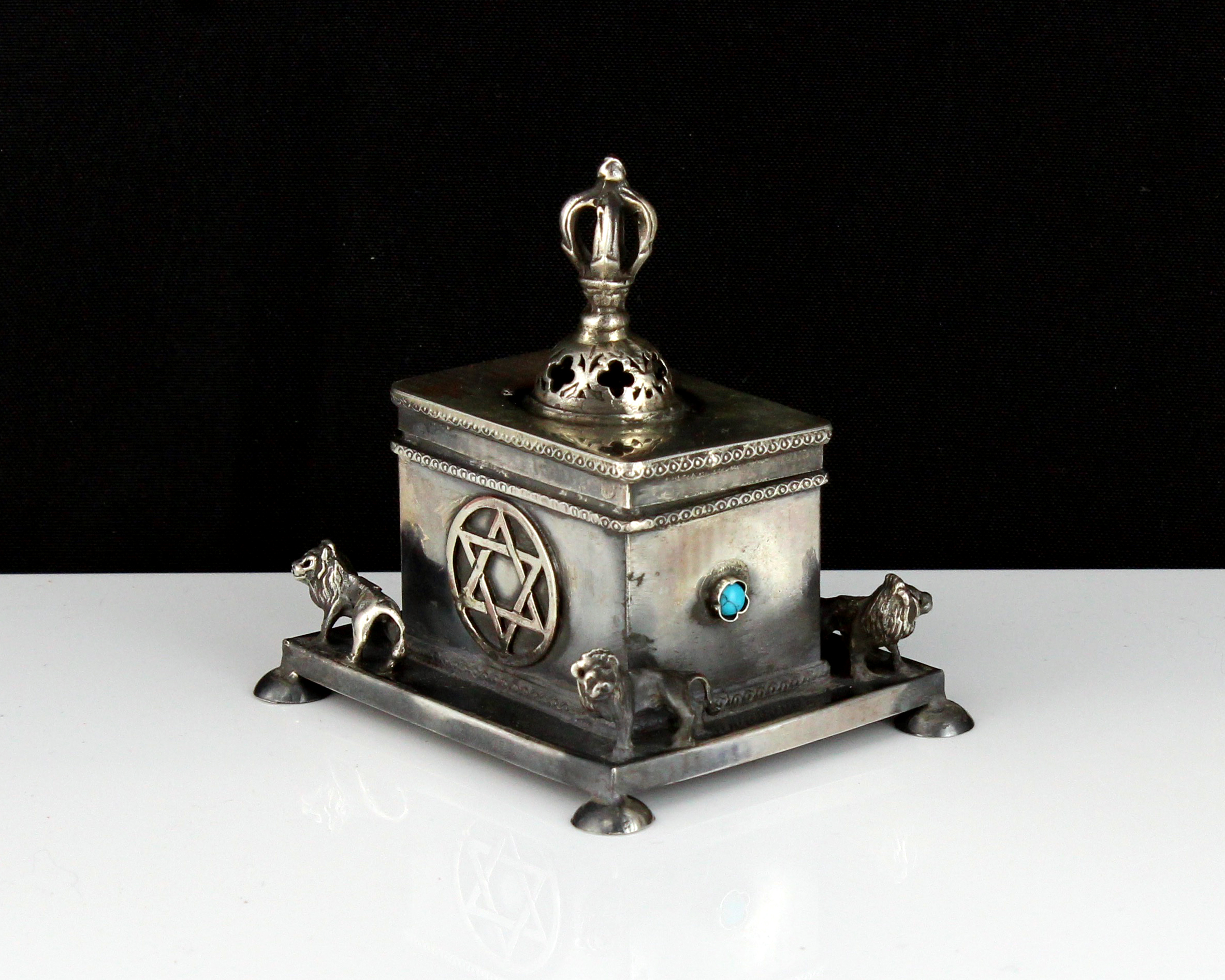 A jewelled silver Judaica box of rectangular form, on a larger base decorated with lions, raised