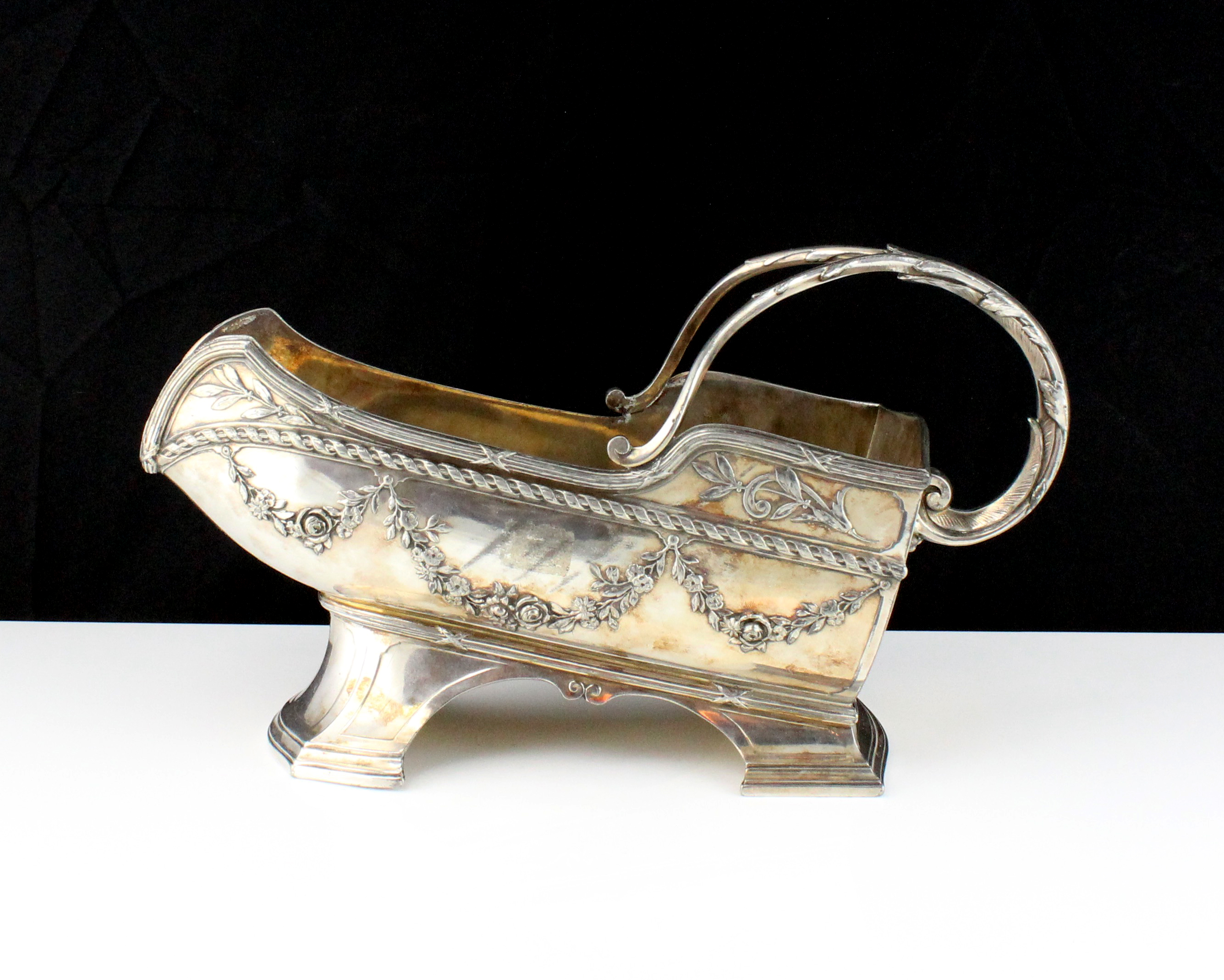 A French silver plated wine bottle holder, decorated with bound reeds and swags / garlands, with