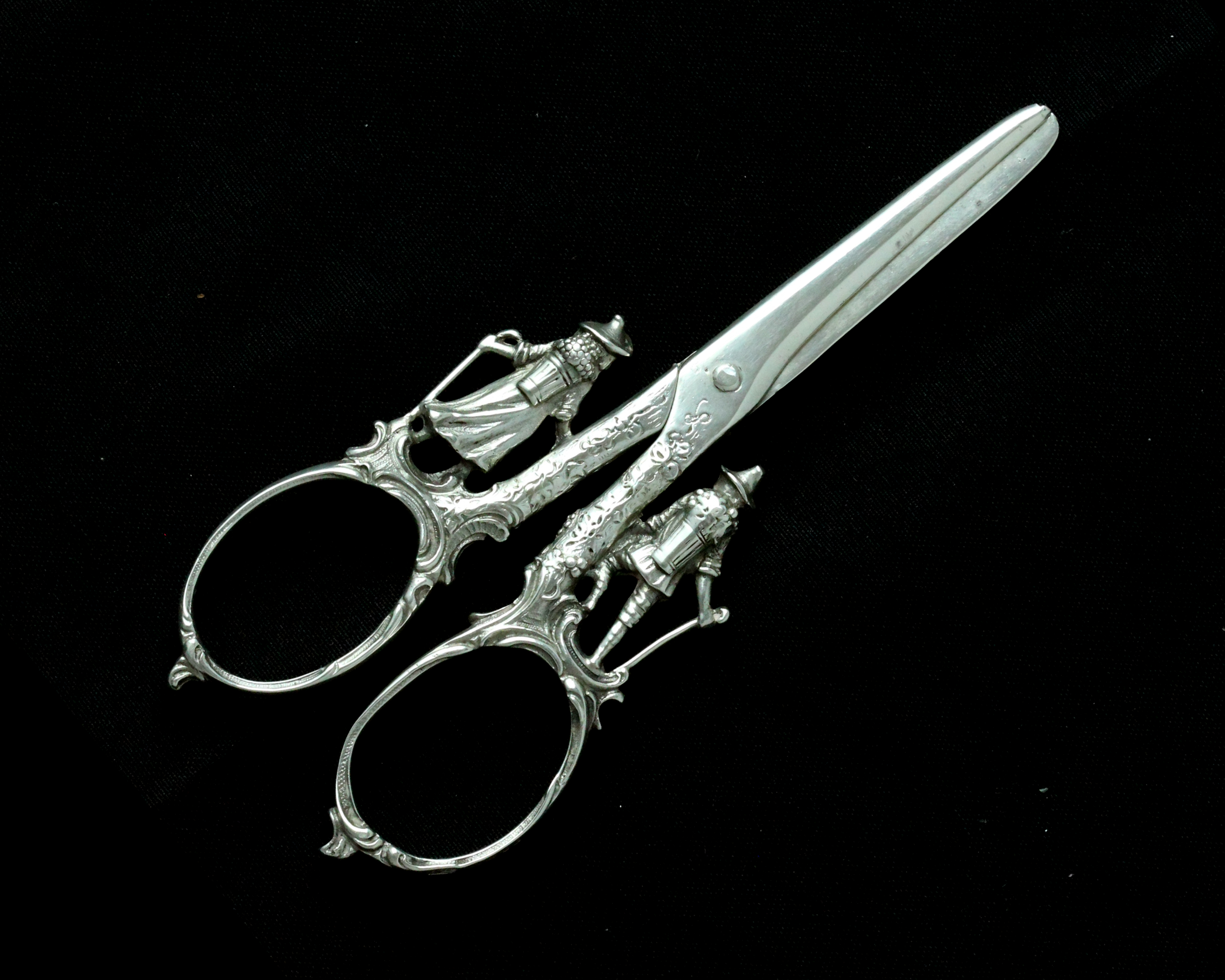 A pair of antique continental silver grape scissors with figural decoration to the handles,