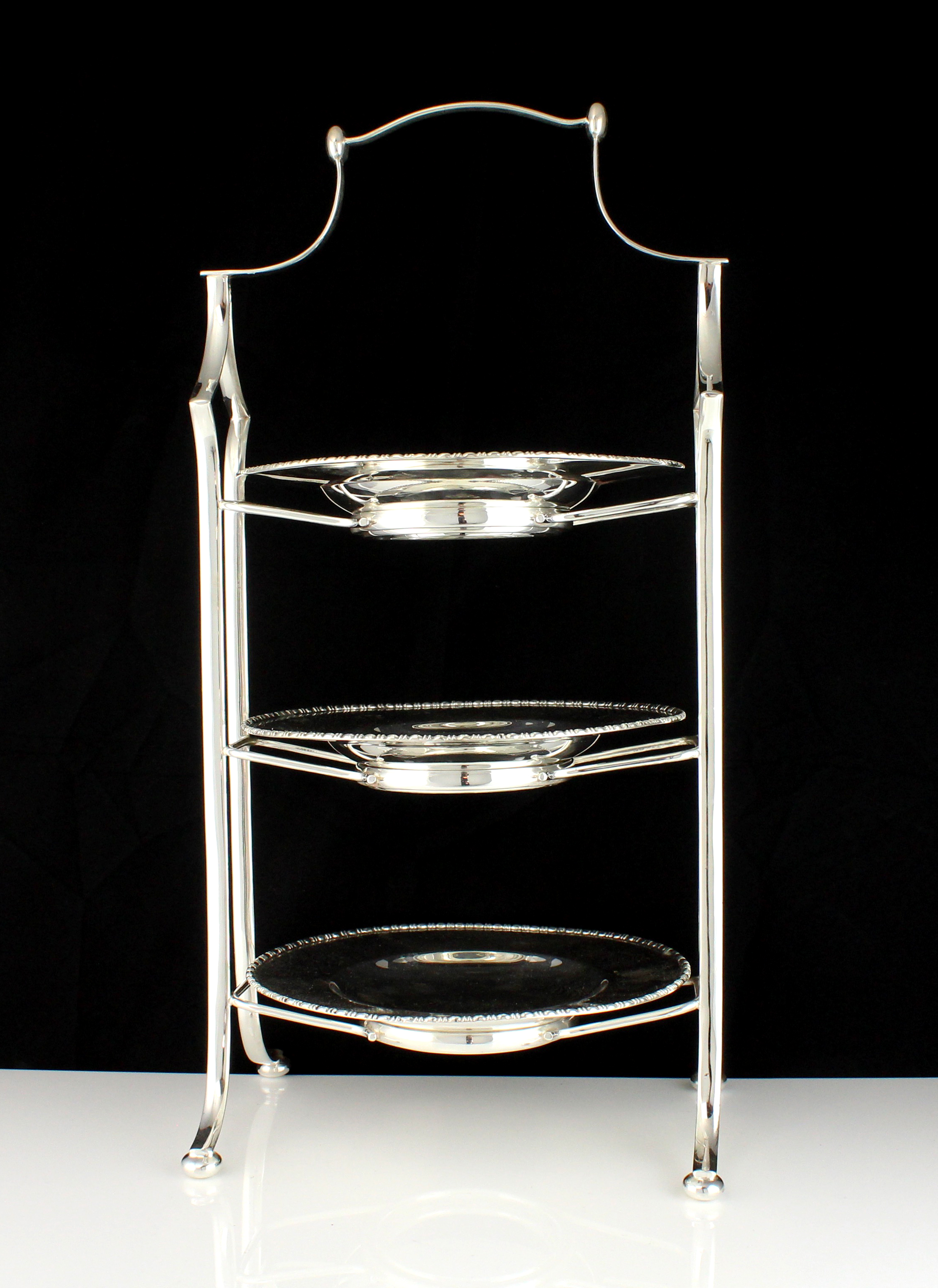 """A large Silver plated cake stand designed with three tiers. Height 51cm / 20""""."""