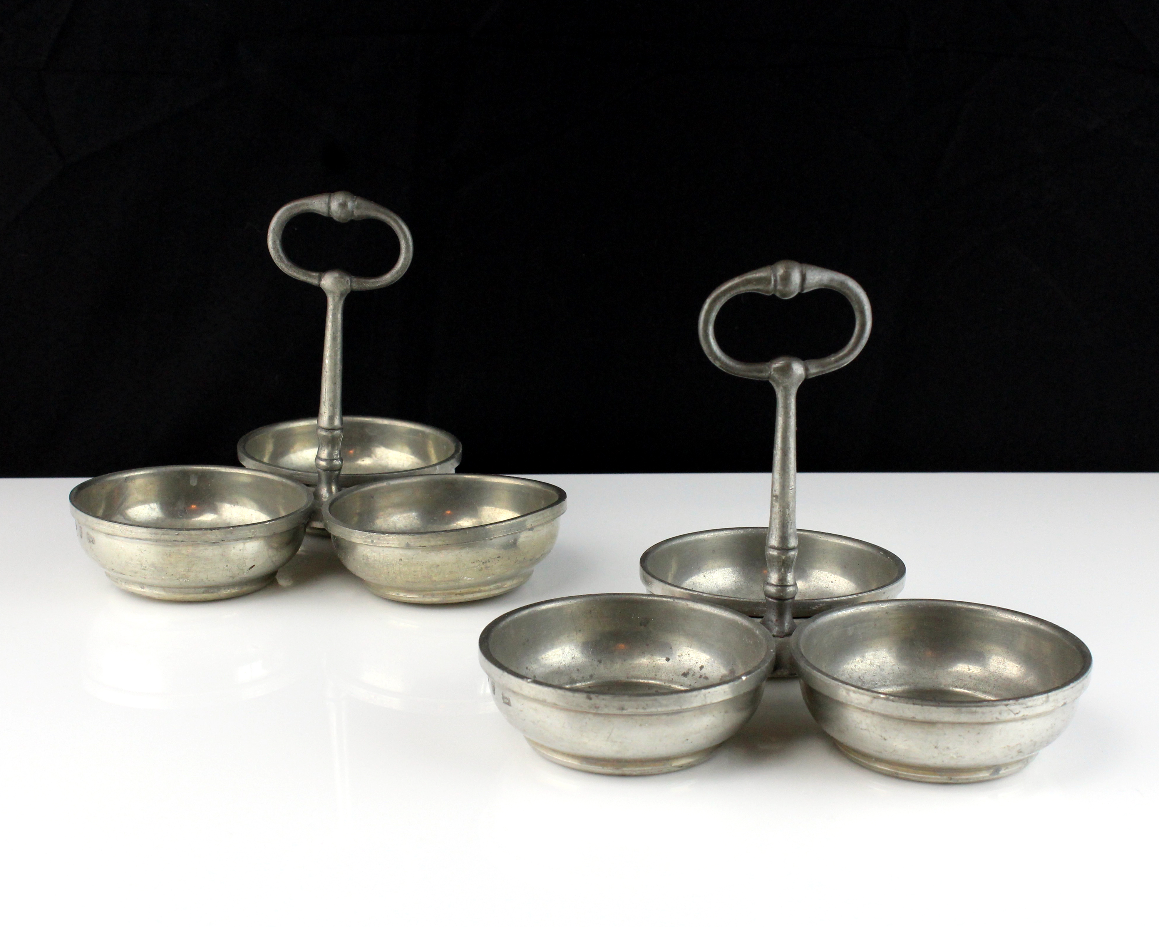 A pair of white metal condiment dishes each designed as a trio of circular dishes with a central