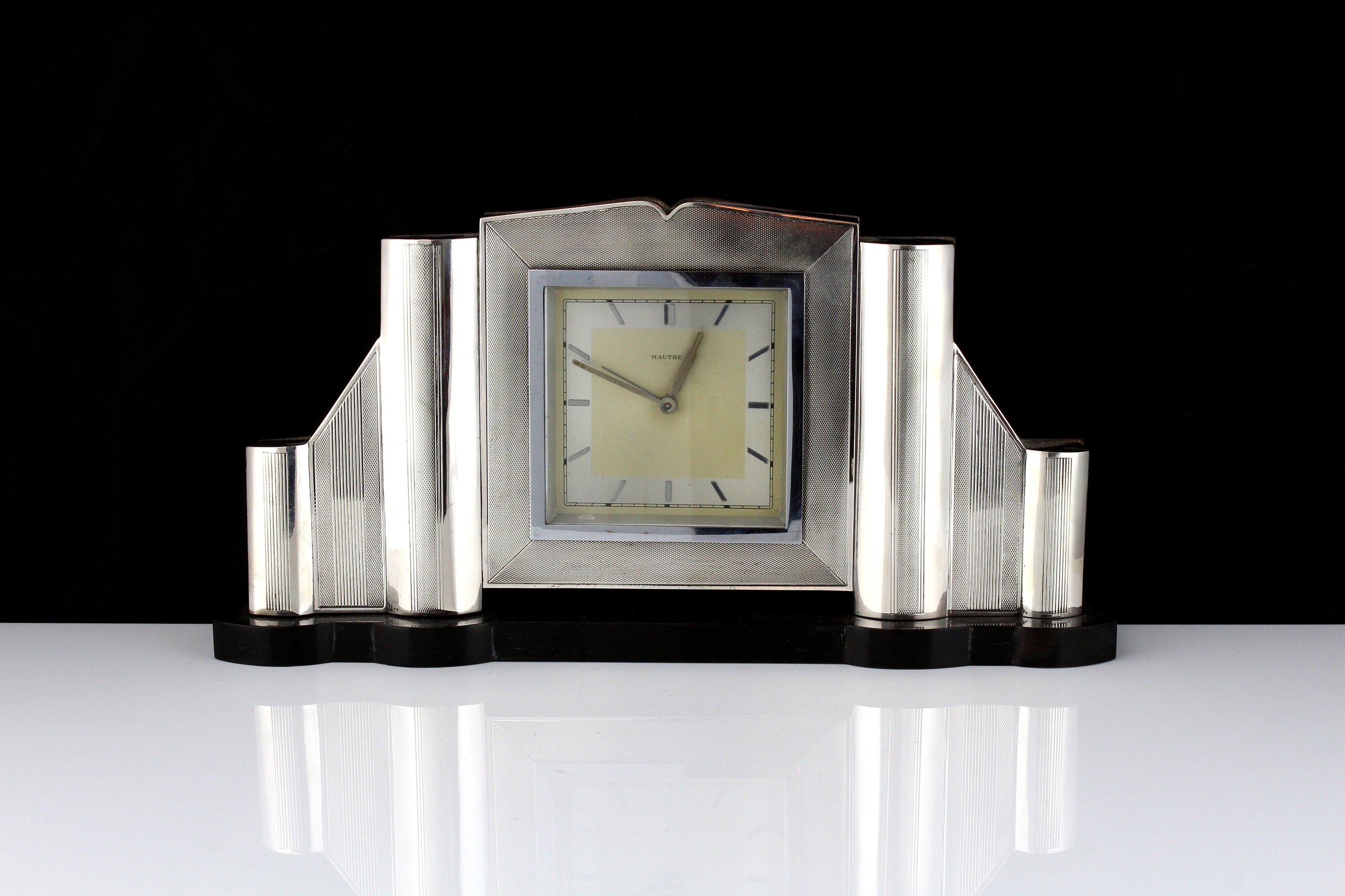 An Art Deco style German Silver mantel clock the geometric body with panels of engine turned