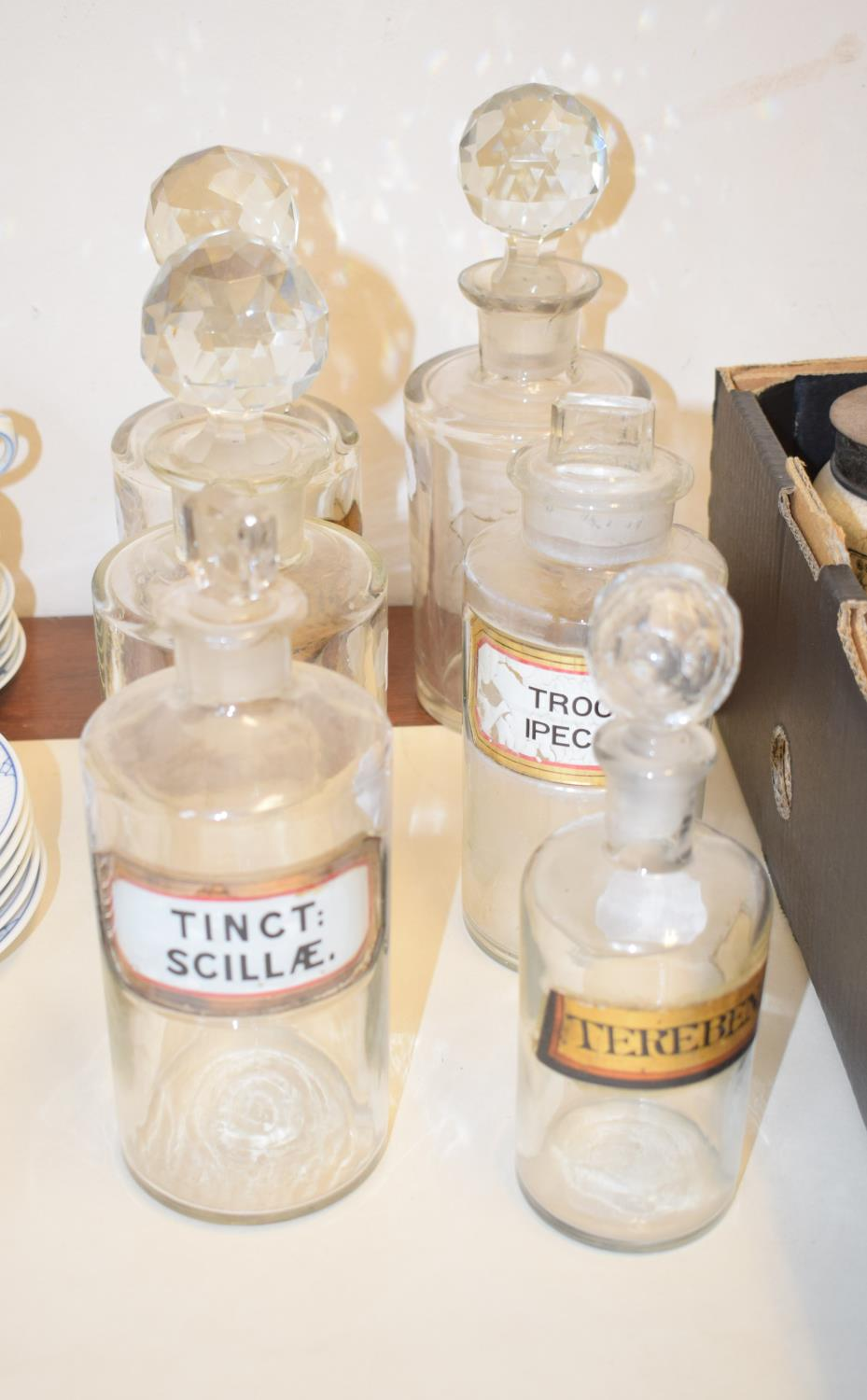 Lot 2 - A set of six Victorian/Edwardian clear glass apothecary bottles, with gilt labels and cut glass