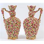 A pair of Zsolnay reticulated vases with handles, decorated flowers and foliage, on four splay