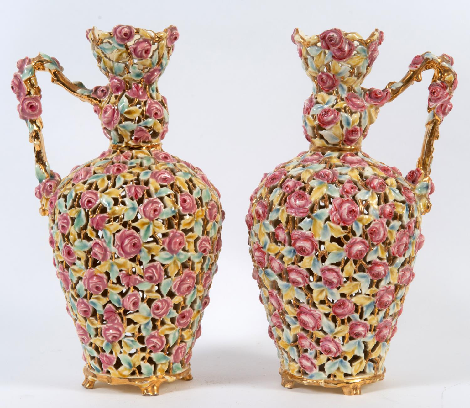 Lot 57 - A pair of Zsolnay reticulated vases with handles, decorated flowers and foliage, on four splay