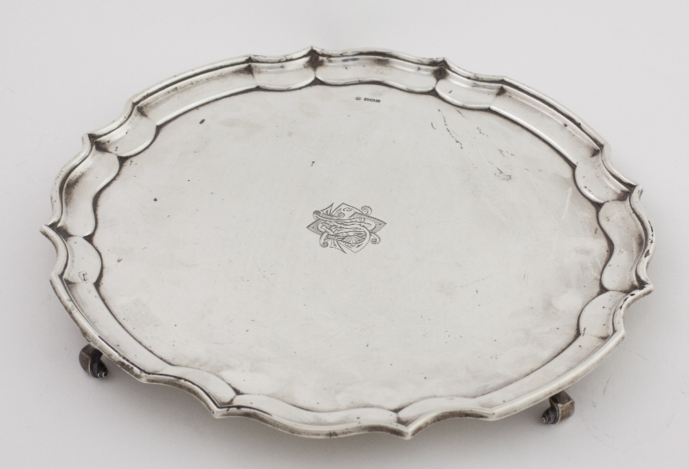 Lot 40 - An early 20th Century large silver Salver, with piecrust edge on scroll feet,