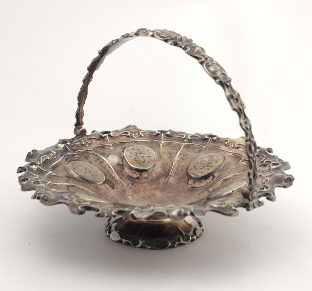 Lot 51 - A very ornate English silver Fruit Basket, with swing handle, and engraved and embossed decoration,