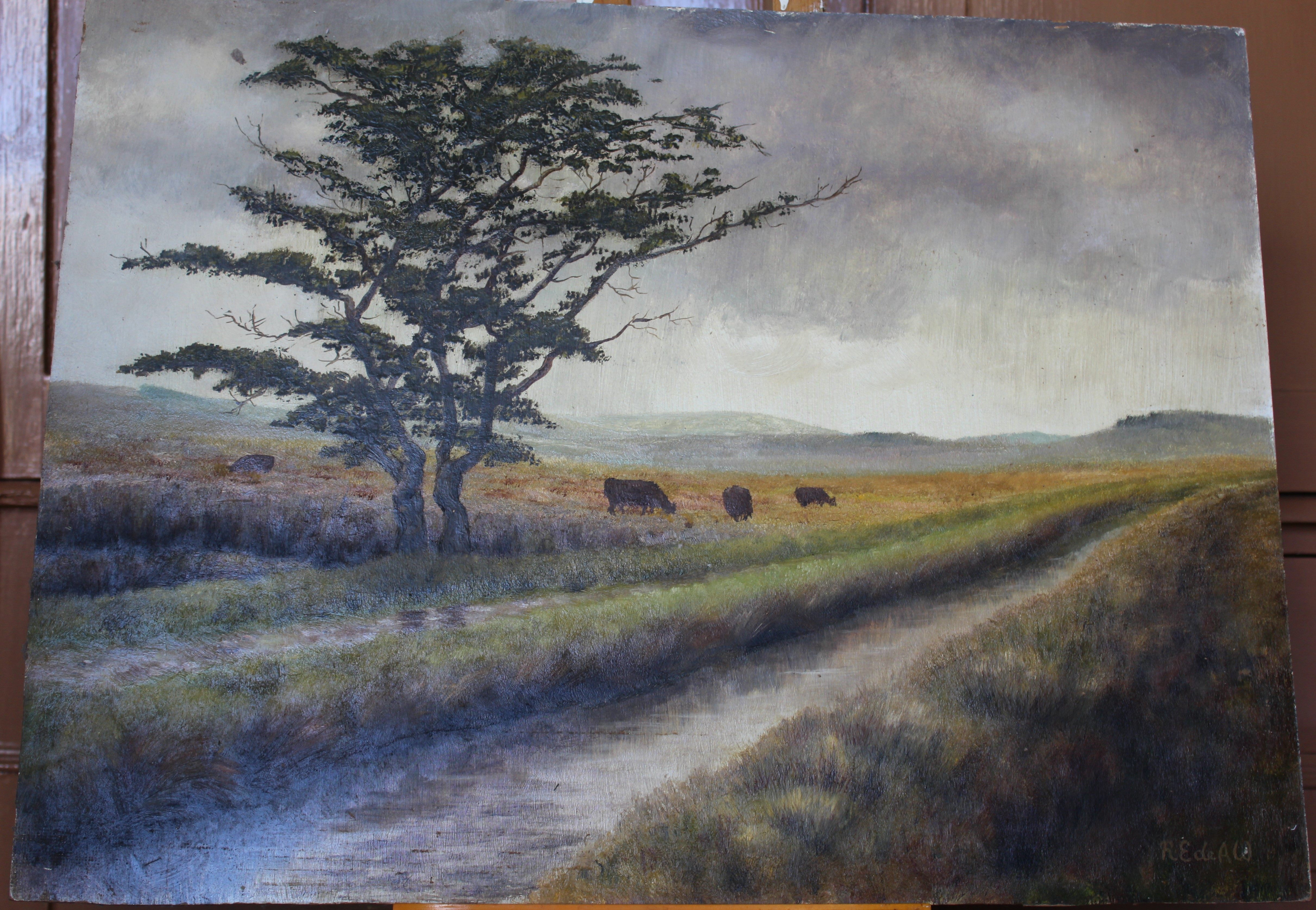 •MOORLAND LANDSCAPE WITH LEAT, TREES AND CATTLE Signed unframed oil on board, 45.5 x 60.5cm.