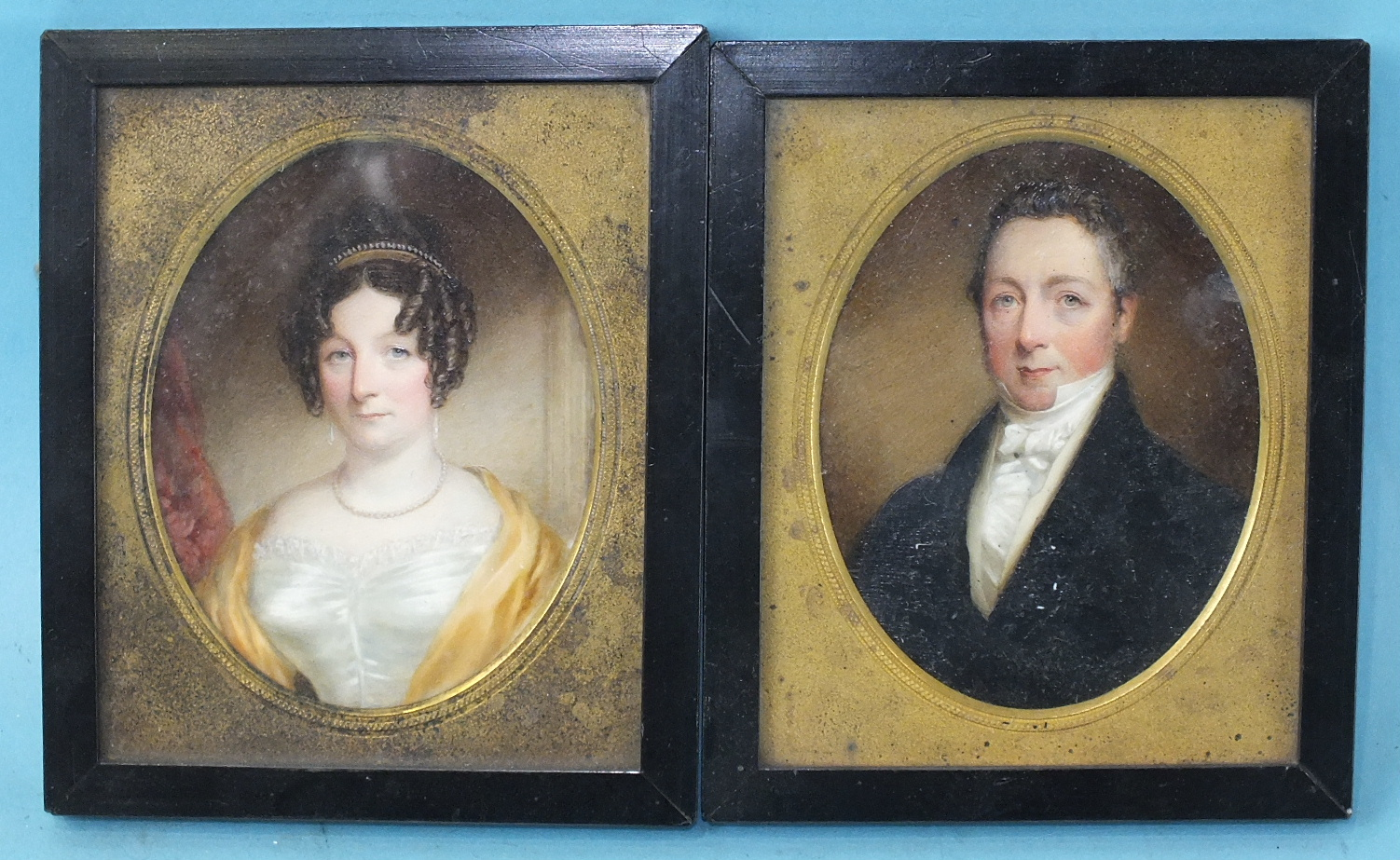 Lot 81 - A pair of 19th century miniature portraits of a gentleman wearing a blue coat and white stock and