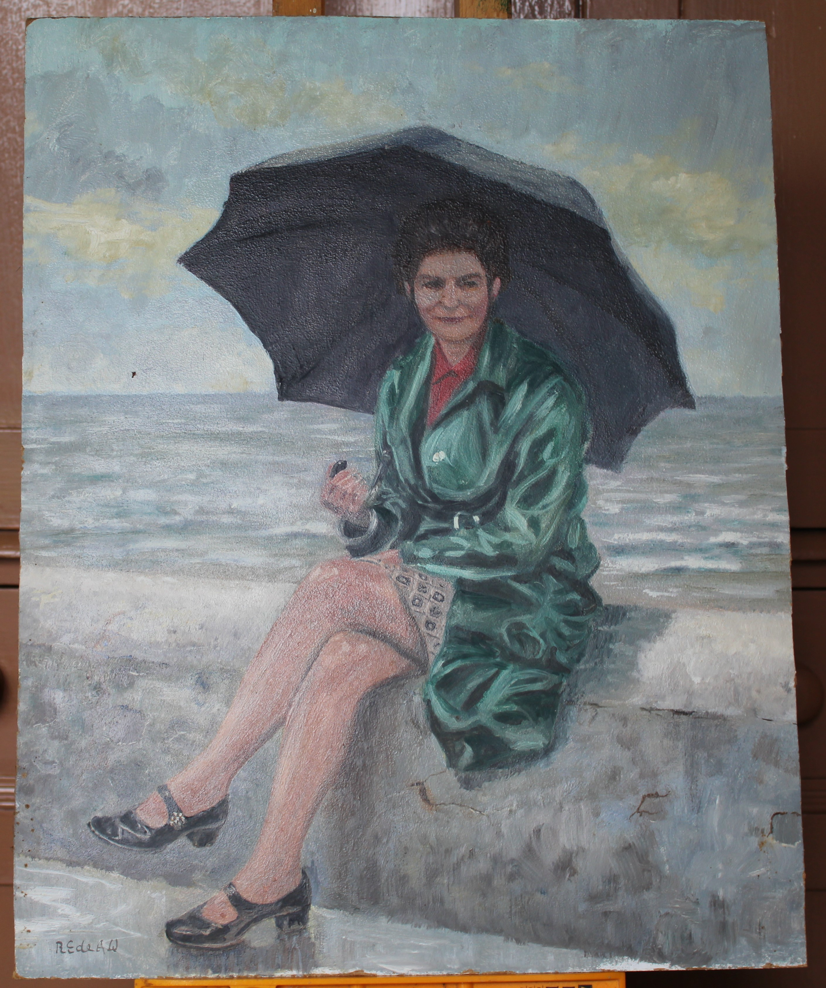 •WOMAN WEARING A GREEN COAT WITH UMBRELLA, SEATED ON A SEA WALL Signed, unframed oil on board, 51