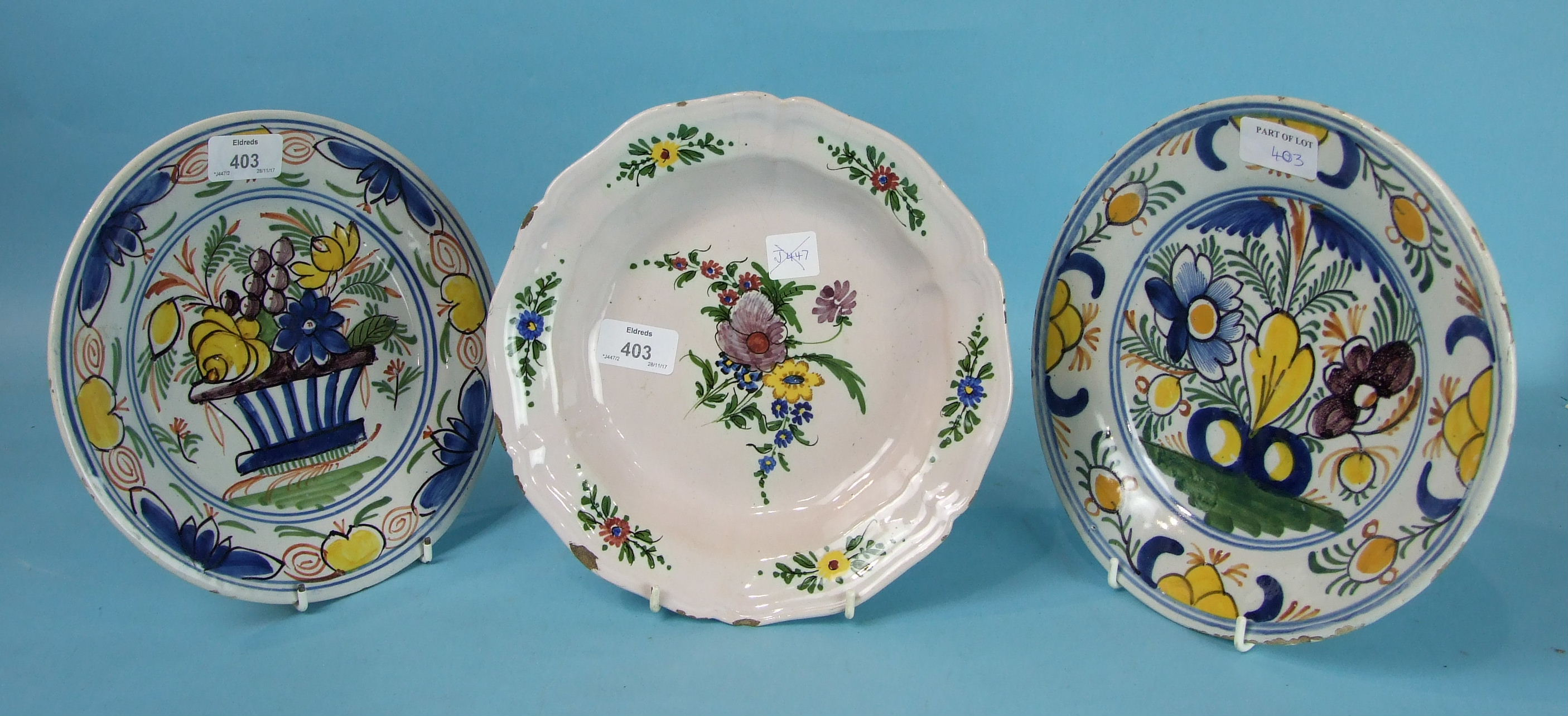 Lot 403 - Three 18th/19th century Dutch Delft plates painted with flowers, (3).