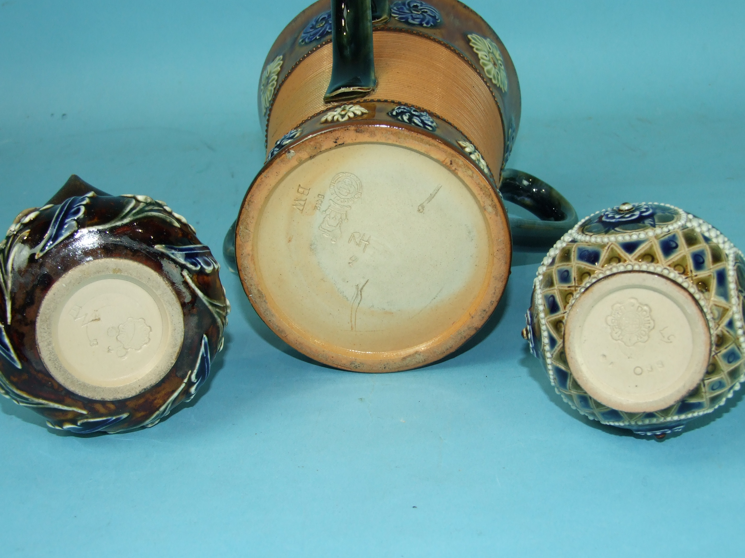 Lot 414 - A Royal Doulton stoneware three-handled tyg of waisted form decorated with bands of blue flower