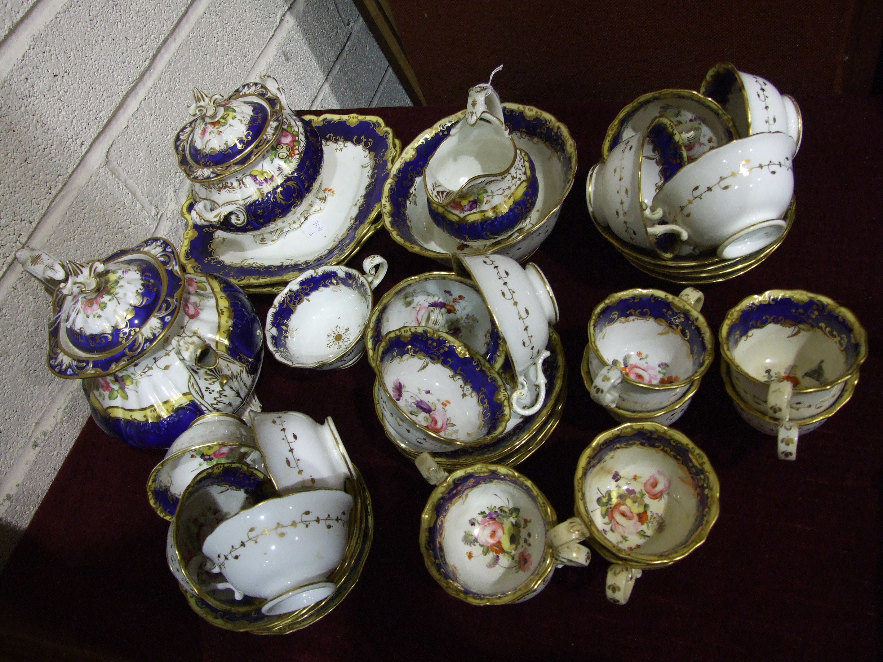 Lot 408 - A mid-19th century English porcelain part tea service decorated with flowers on a blue, yellow and
