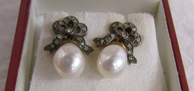 Pair of bow topped diamond & pearl earrings