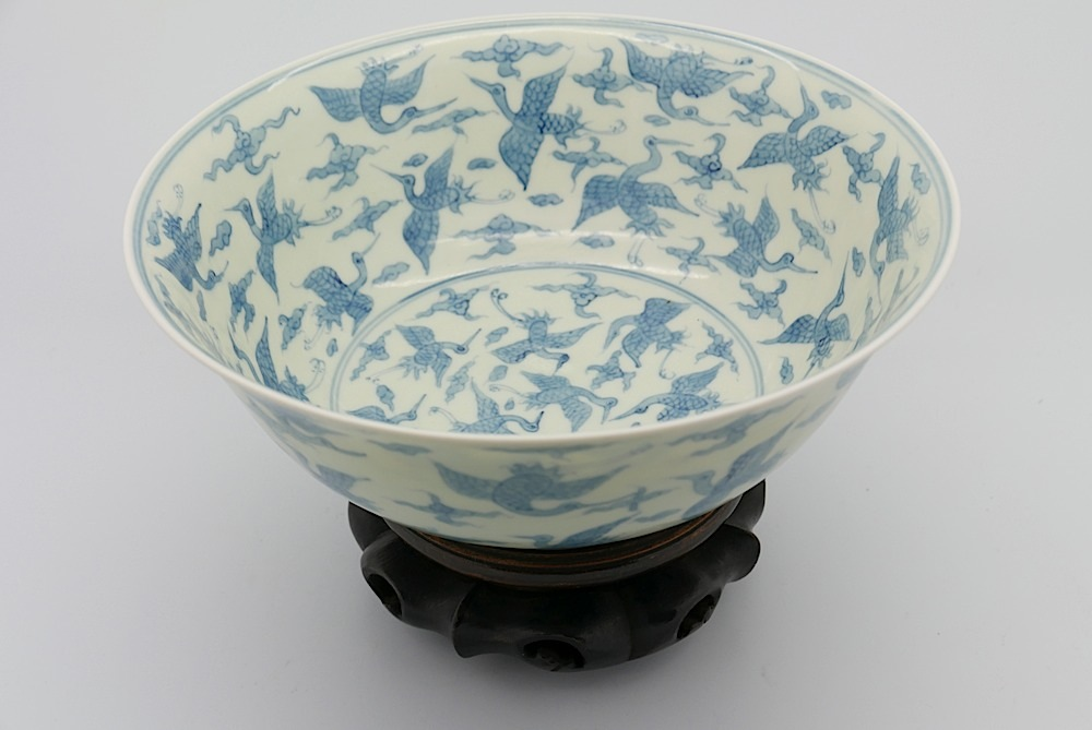 Lot 62 - A Chinese blue & white bowl, raised on tubular foot, decorated with storks in flight framed by