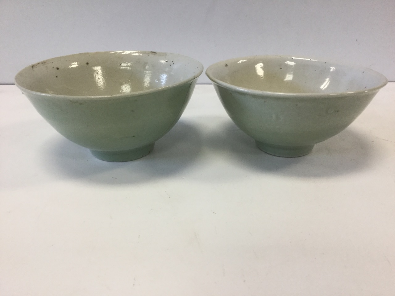 Lot 23 - A pair of early Chinese celadon glazed bowls, raised on tubular bases, unmarked and one