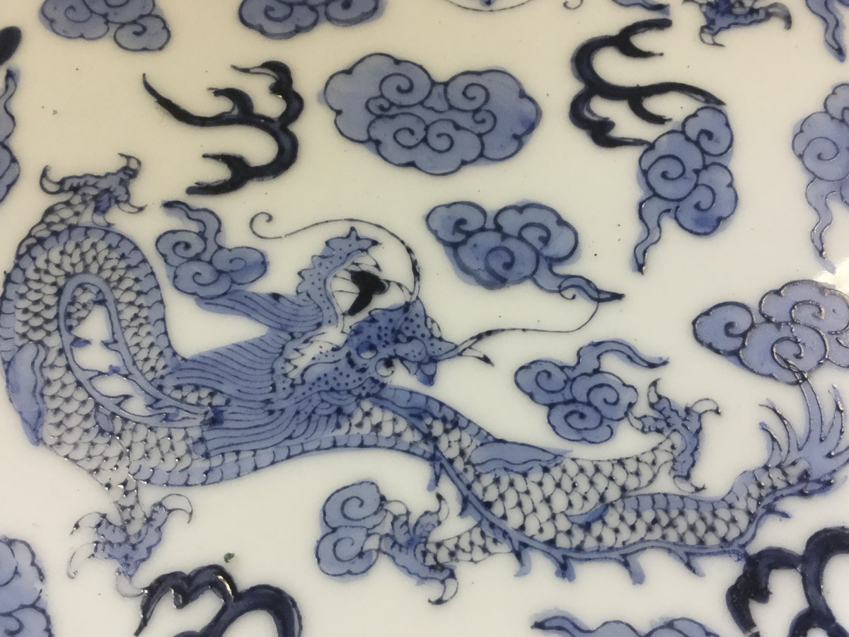 Lot 74 - A Chinese blue & white plate decorated with two four-clawed dragons, on bat & cloud design ground