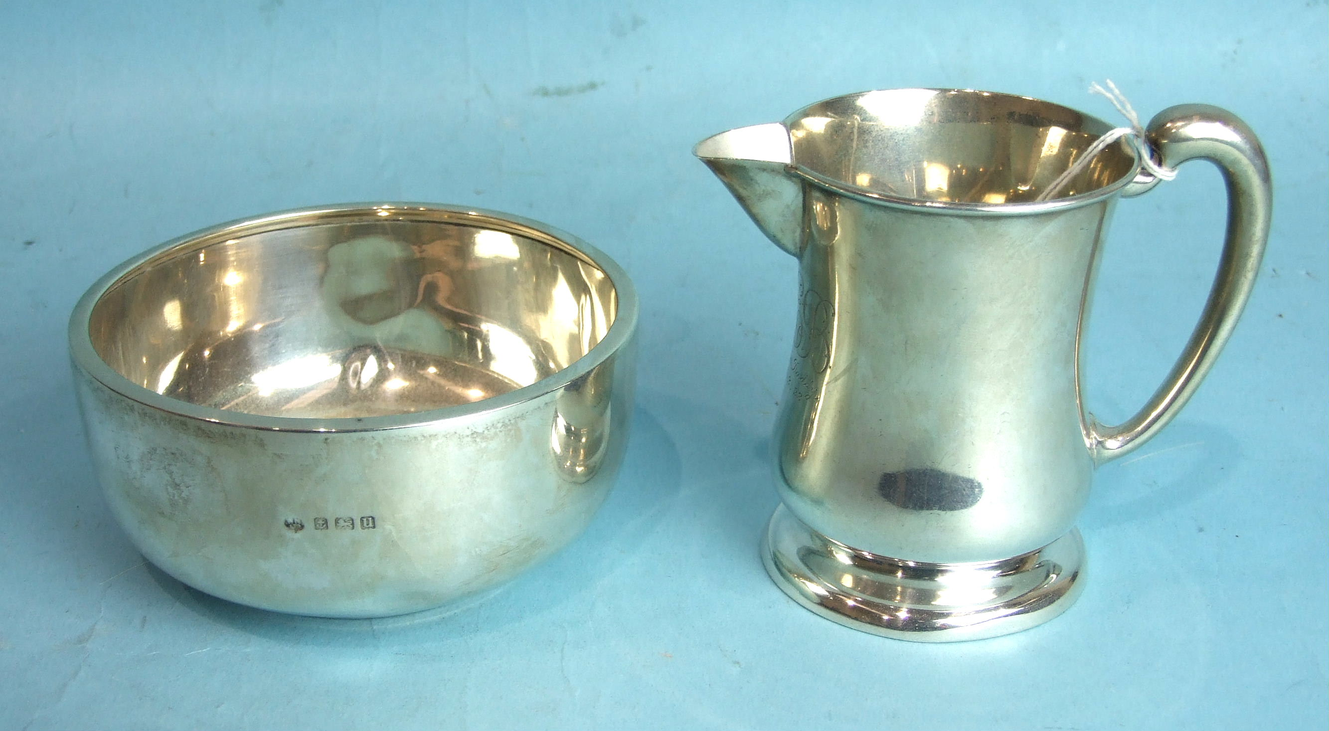 Lot 232 - A silver sparrow beak cream jug of plain form, with inscription, 9.5cm high, Birmingham 1921 and a
