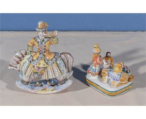 A pair of Russian decorated folk art pottery figures, one depicting a Cossack on horseback and the other a family eating a me