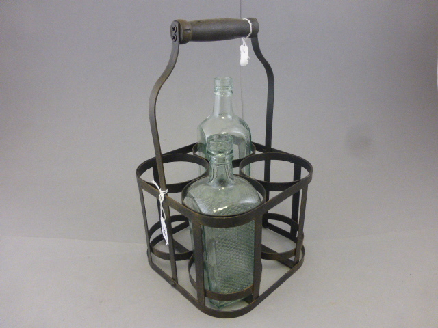 Lot 29 - A metal bottle holder, with two glass bottles and carry handle
