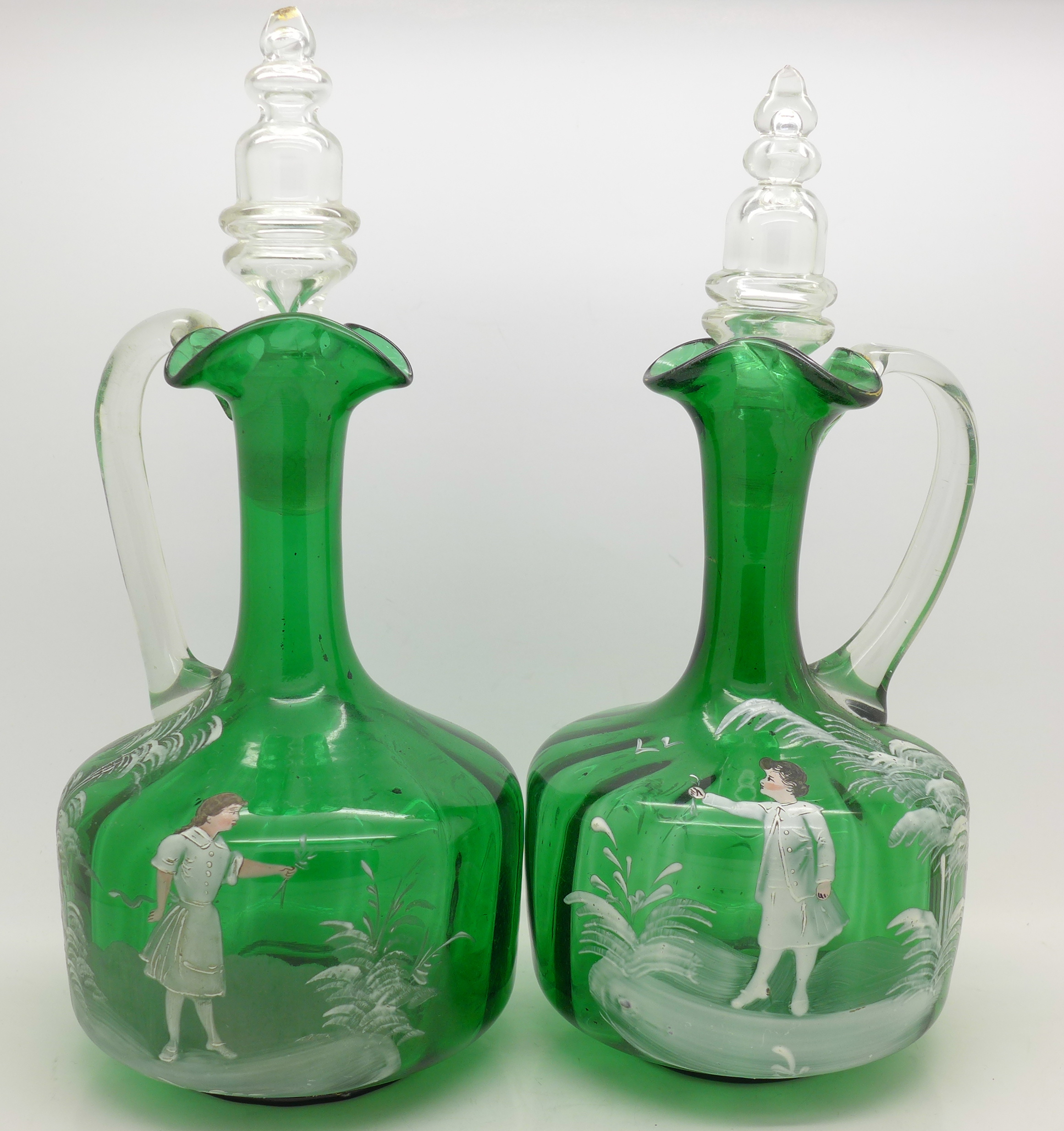 Lot 603 - A pair of green glass Mary Gregory jugs with stoppers