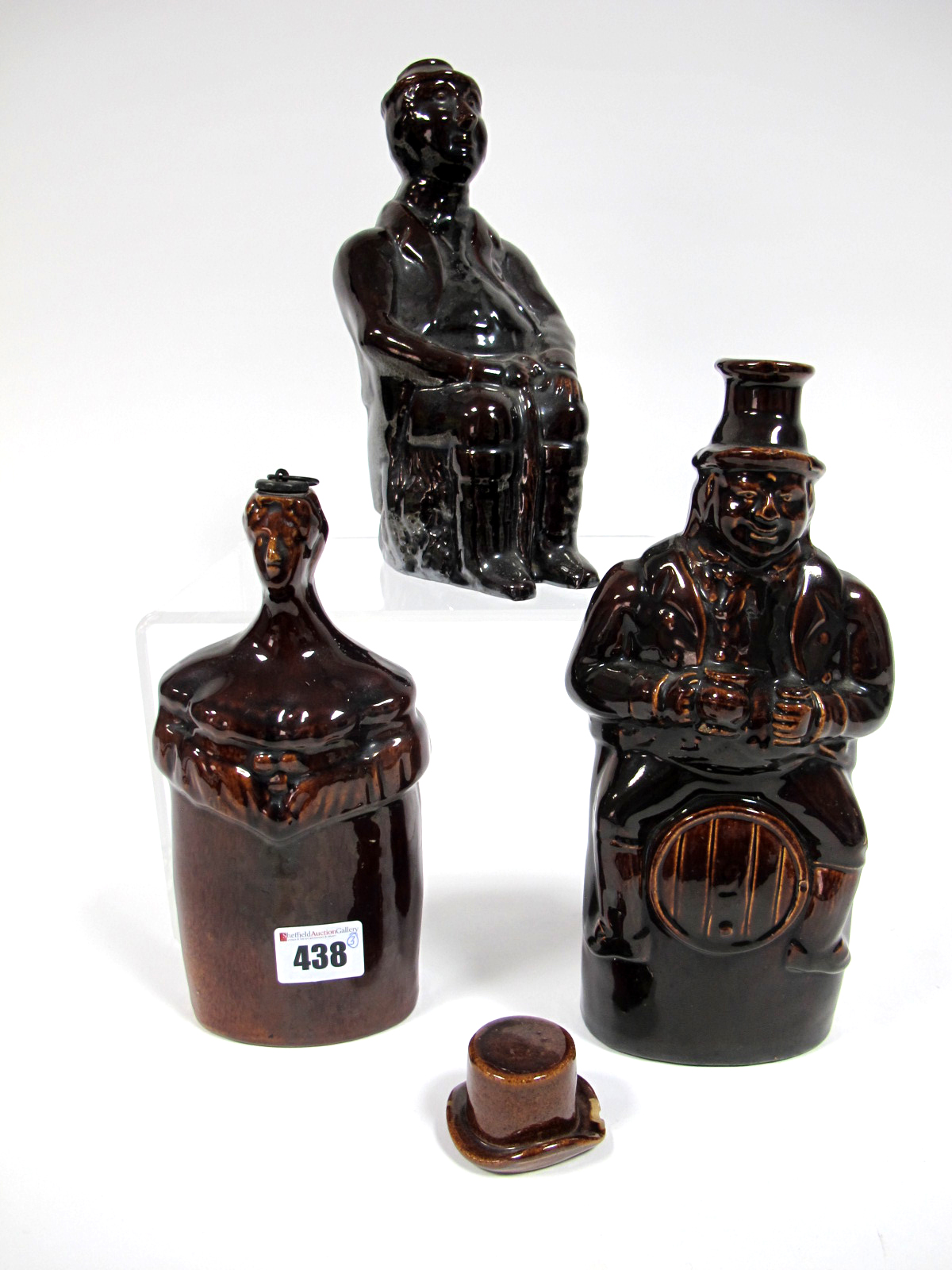 Lot 438 - A Mid XIX Century Treacle Glazed Stoneware Flask, modelled as a gentleman seated astride a barrel,