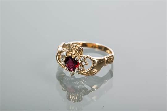 NINE CARAT GOLD HEART MOTIF RUBY RING modelled as two hands