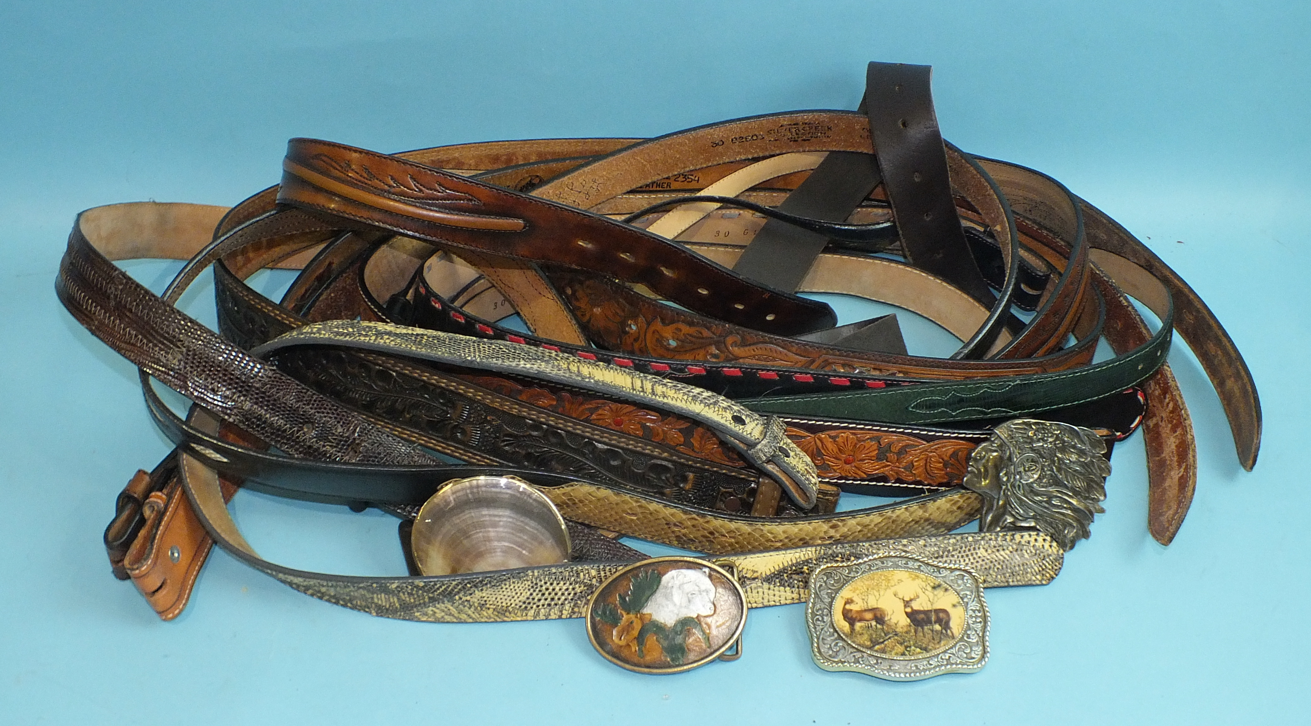 Lot 543 - A collection of eleven Tony Lama and other tooled-leather belts and four decorative belt buckles, (