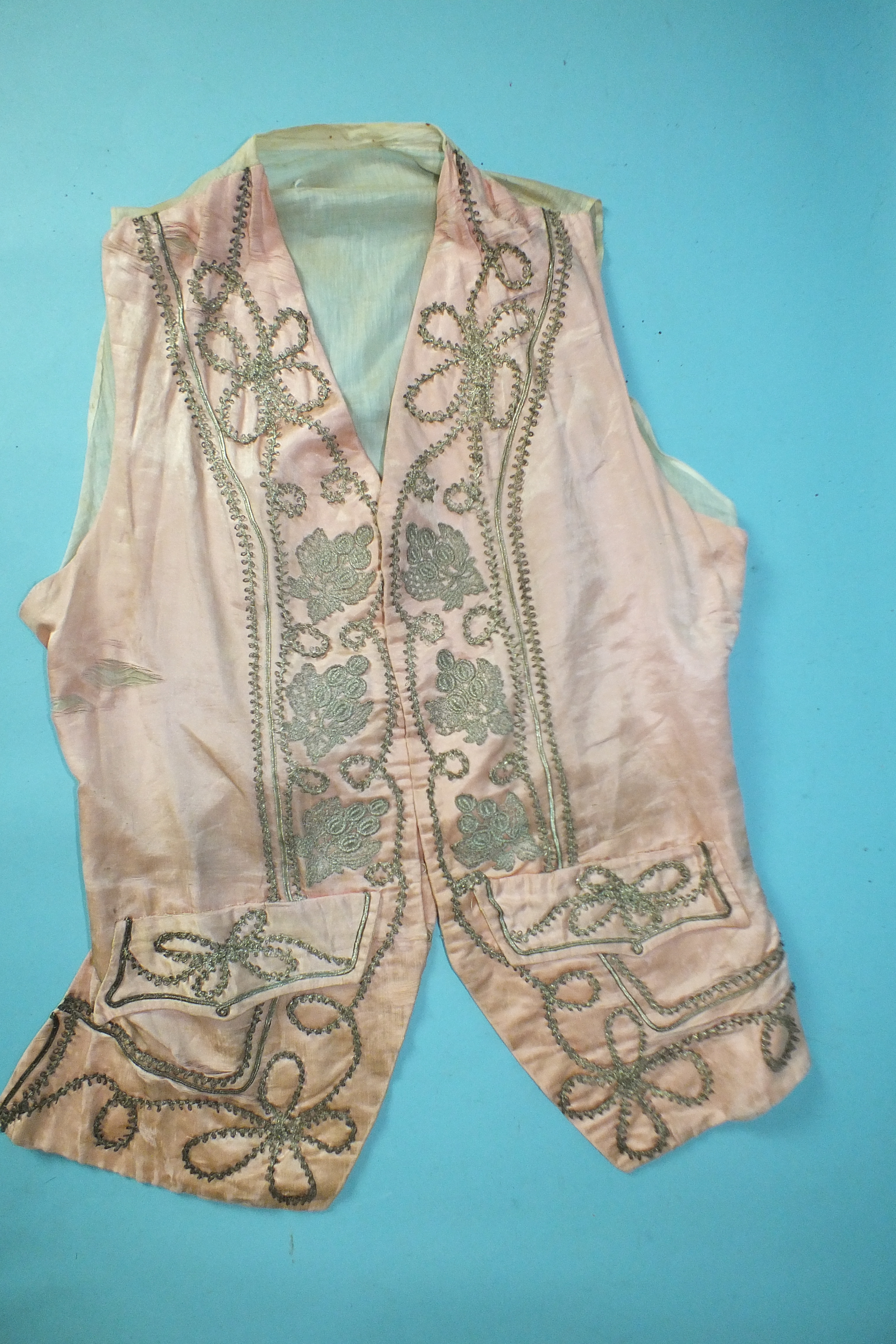A late-18th century pale pink silk waistcoat, the front panels with applied silver lace and braid,