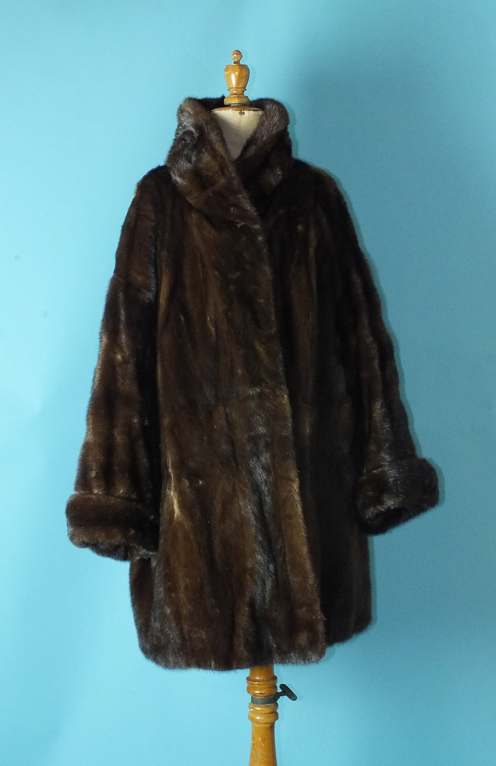 A lady's brown mink coat, three-quarter length, with turned-up cuffs and roll neck, labelled for
