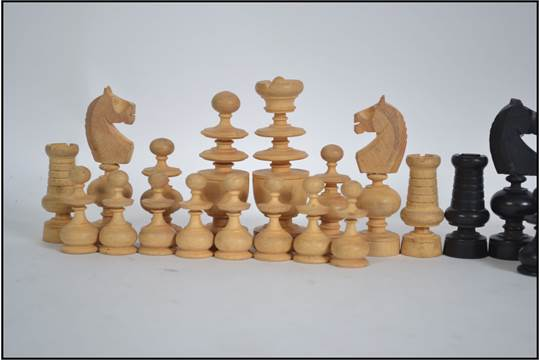 An ebony and boxwood chess set of unusual form in the manner