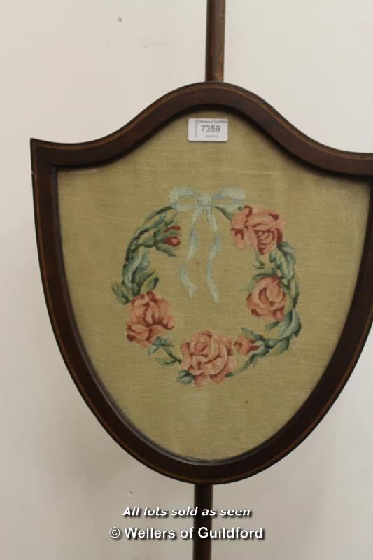 Lot 7359 - An Edwardian inlaid mahogany shield shaped polescreen on three curving supports.