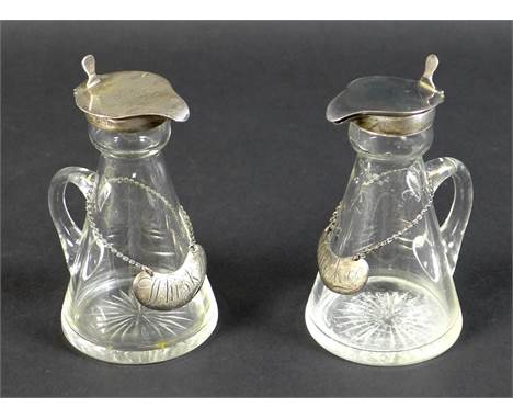 A pair of Edwardian clear glass and silver mounted noggin flasks, each of tapering form with mounted hinged lid, spout and th
