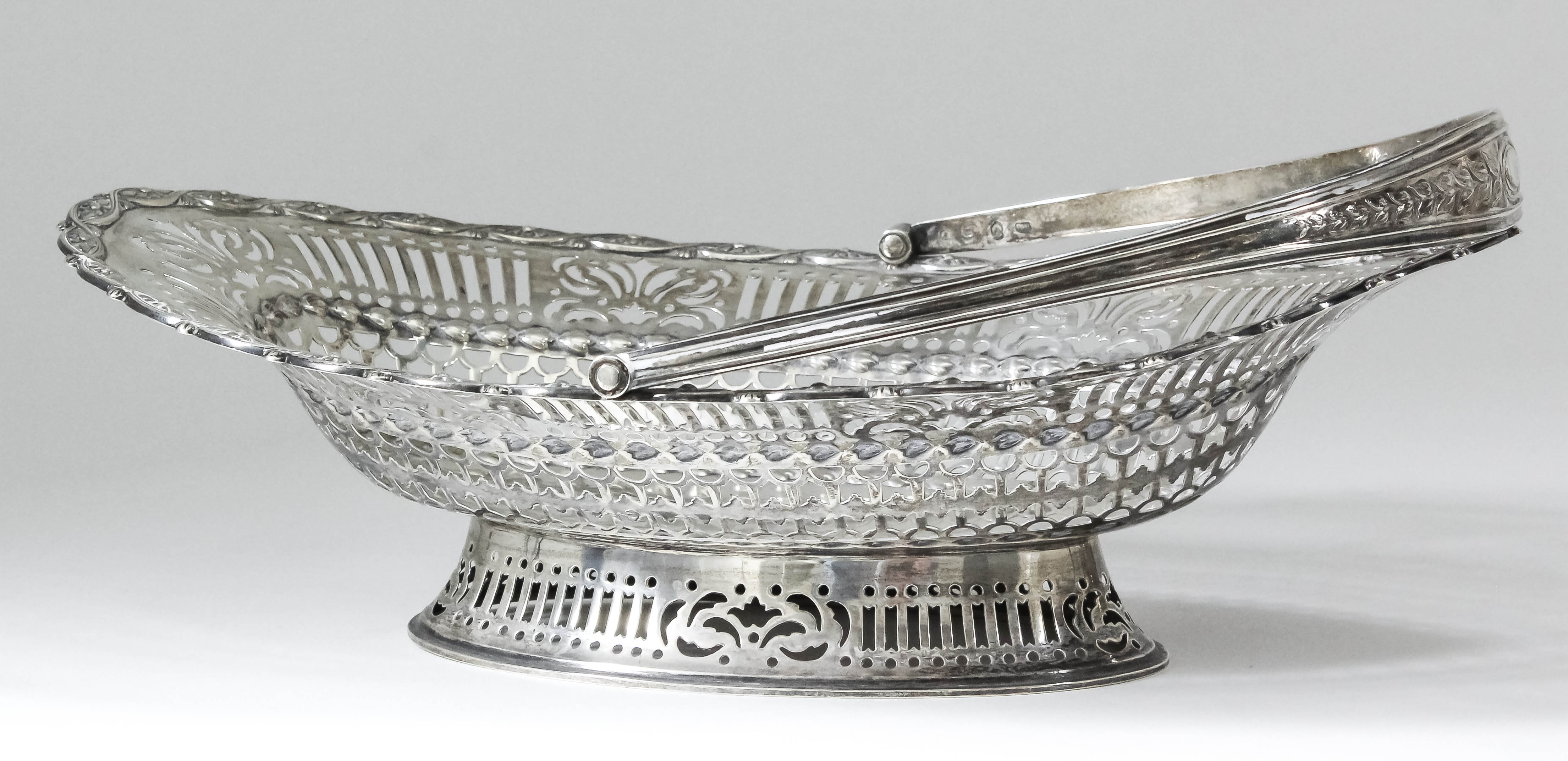 """Lot 21 - A George V Scottish silver oval cake basket of """"George III"""" design, with pierced sides and ovoid"""