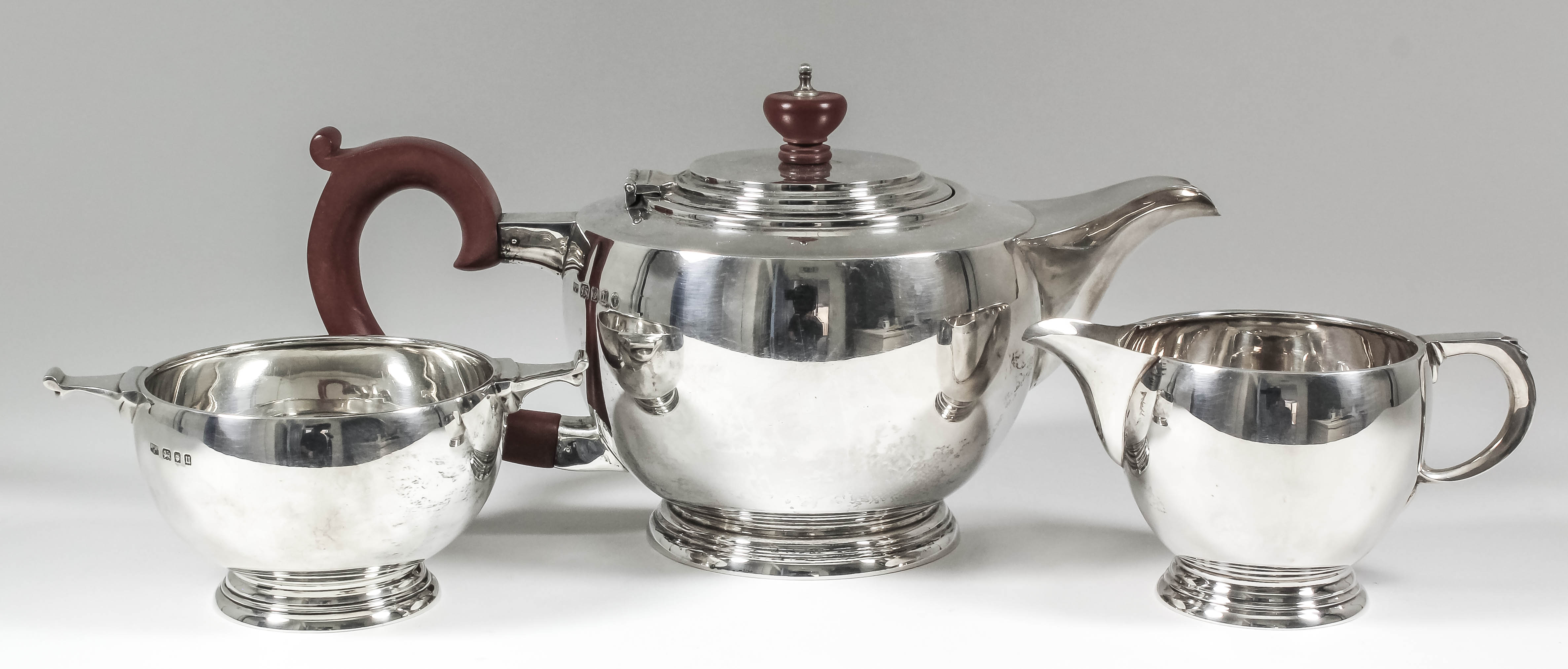 Lot 3 - A George V silver circular three-piece tea service of Art Deco design of bulbous form, with scroll