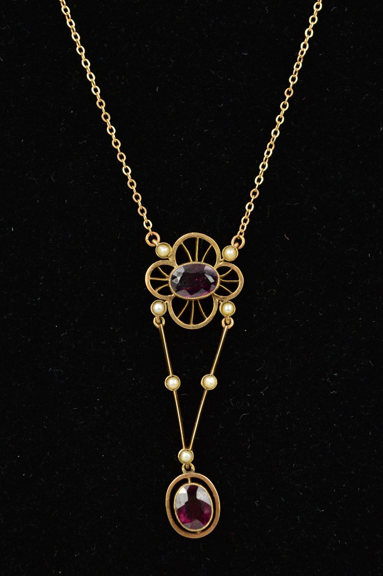 Lot 31 - AN EARLY 20TH CENTURY GOLD GEM PENDANT designed as an oval garnet within an open flower shape