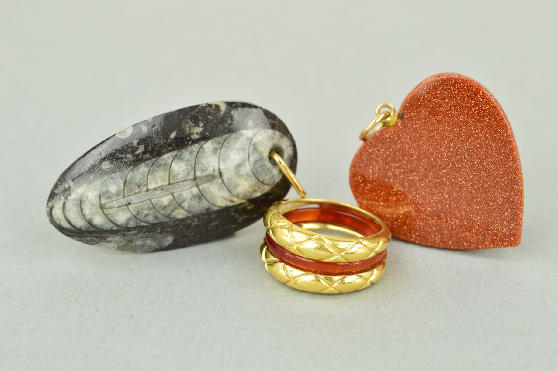 Lot 58 - TWO PENDANTS AND A RING to include a goldstone heart, a fossil pendant and a dress ring which has an