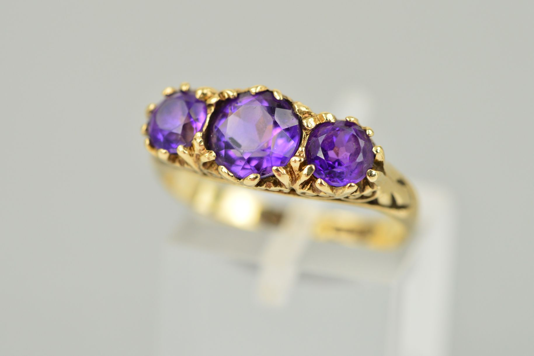 Lot 37 - A MID TO LATE 20TH CENTURY THREE STONE AMETHYST RING, scroll detail to shoulders and sides, ring
