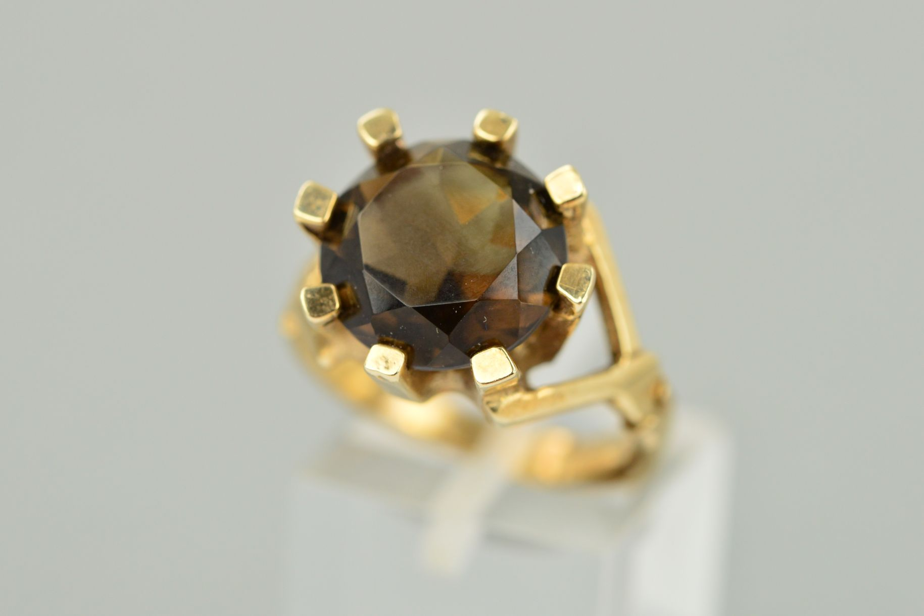 Lot 40 - A 9CT GOLD SMOKY QUARTZ RING, the circular smoky quartz within a thick eight claw setting with a