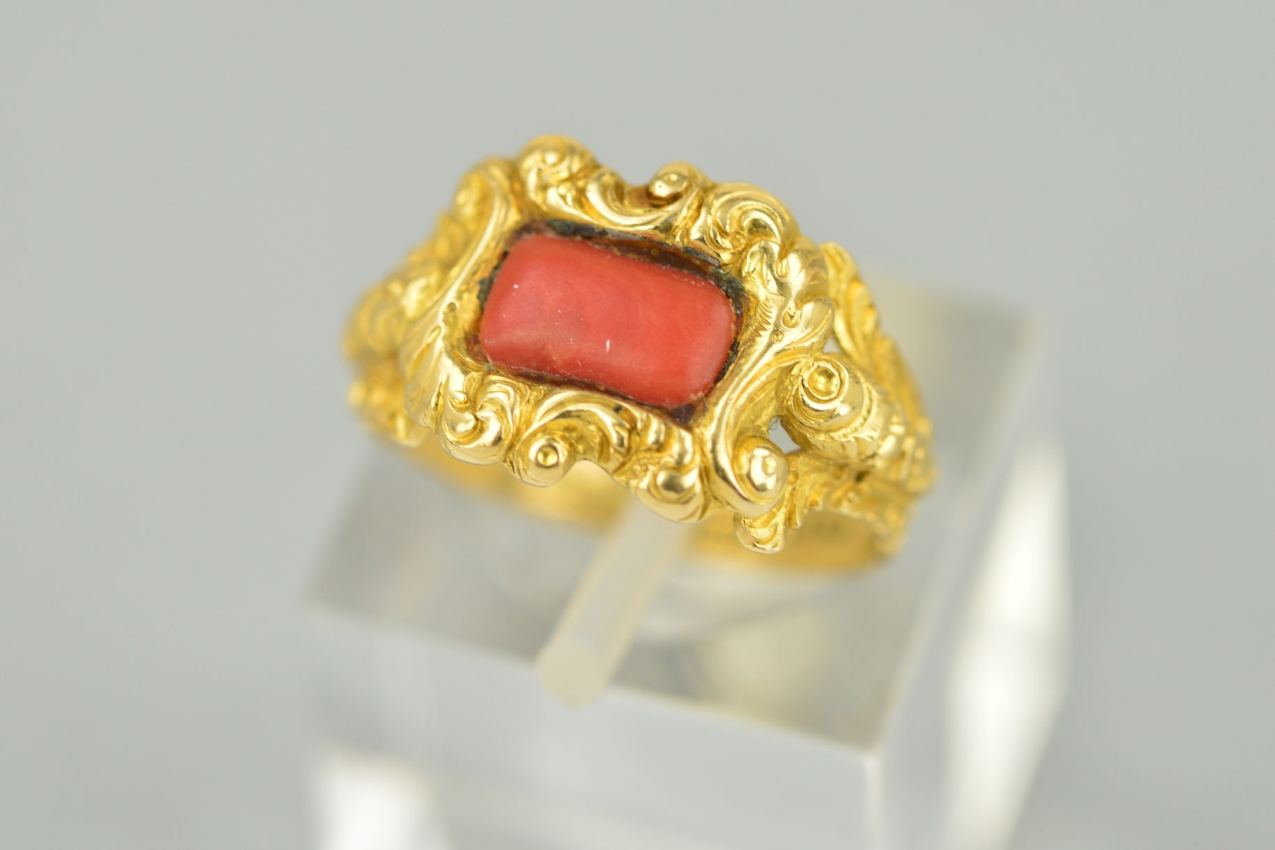 Lot 54 - A LATE GEORGIAN GOLD AND CORAL RING, centering on rectangular coral stone (which is a likely later