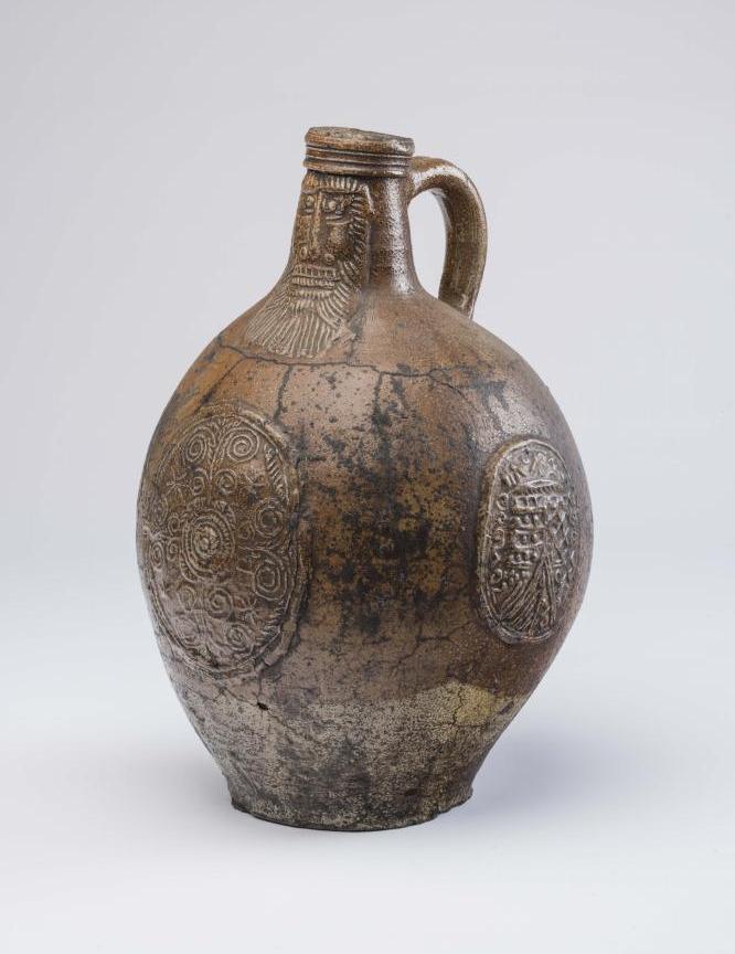 Lot 25 - A RHENISH SALTGLAZE STONEWARE BELLARMINE/BARTMANNS KRUG, late 16th century, of ovoid form, the