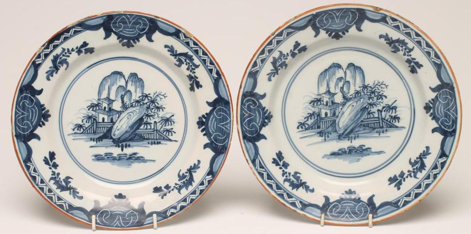 Lot 27 - A PAIR OF DELFT PLATES, late 18th century, painted in blue with a pagoda, fence and rocks within a