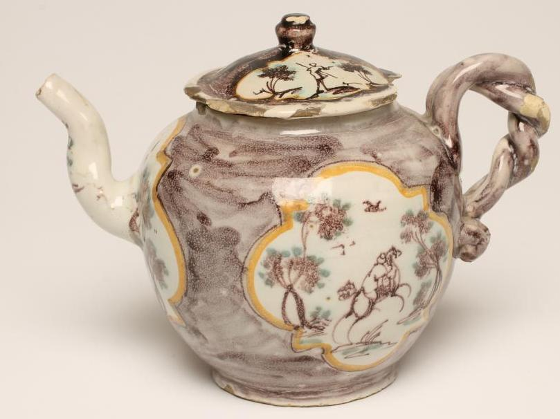 Lot 28 - AN ITALIAN FAIENCE TEAPOT AND COVER, late 18th century, probably Savona, of globular form with