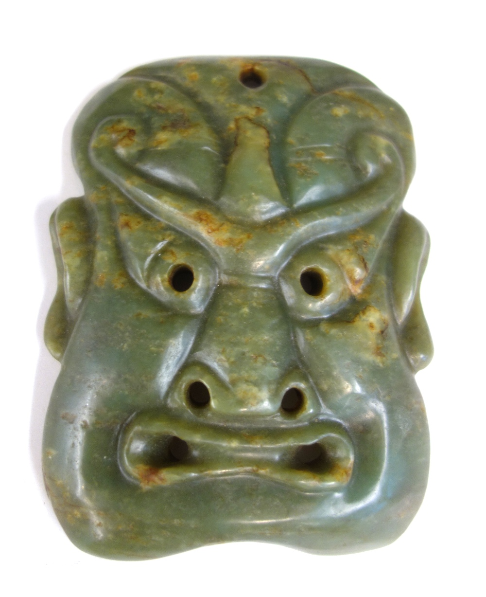 Lot 1363 - A Chinese jade mask, carved as a grimacing face, with pierced eyes, nostrils and mouth, 15cm.high.