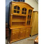 STAINED PINE DISPLAY CABINET, THE TOP FITTED WITH THREE GLAZED DOORS WITH OPEN SHELF, THE BASE